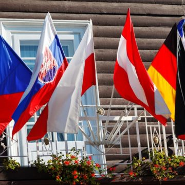 Un hotel europeo con molte bandiere fuori dalla finestra