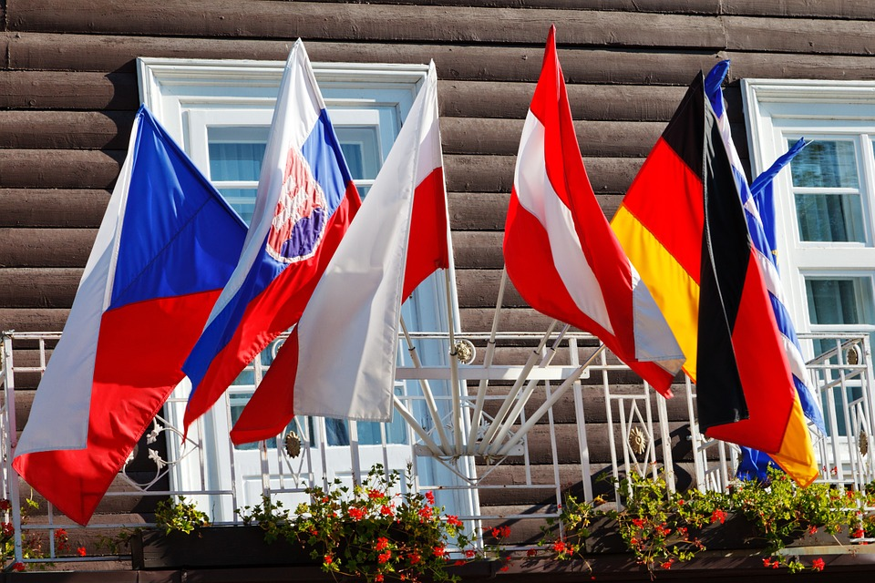 a European hotel with multiple flags out front its windows