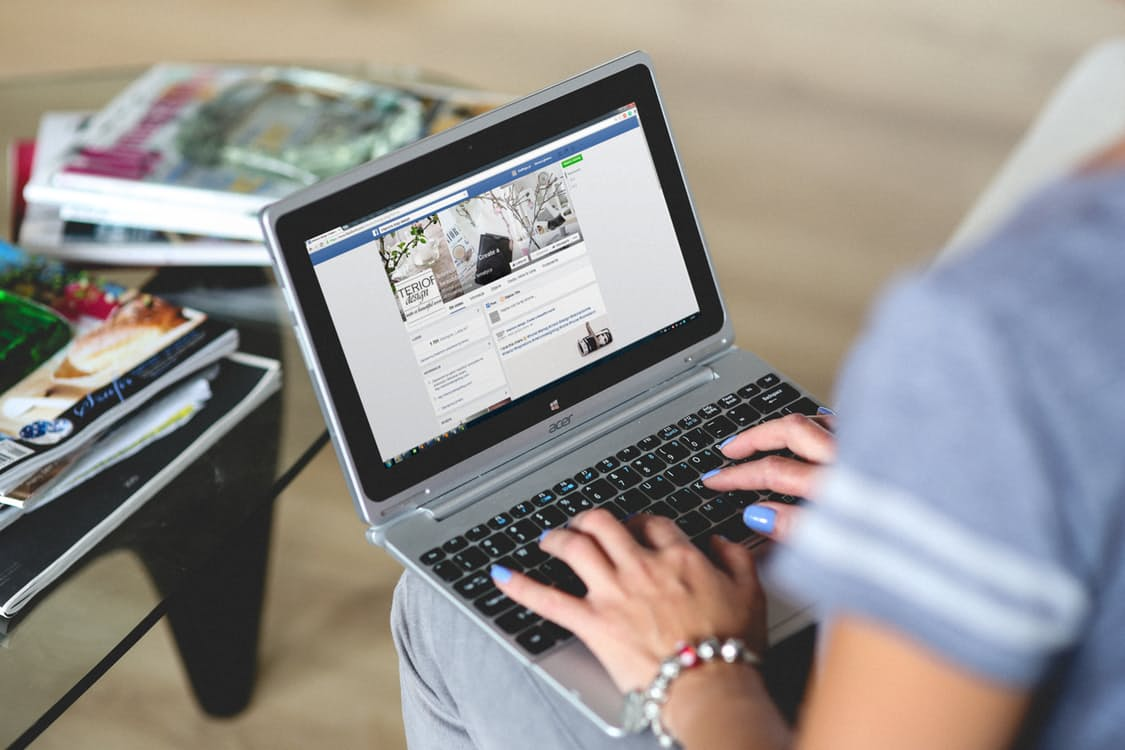 A person uses a laptop to manage their facebook CTA button