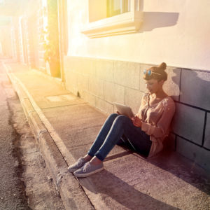 a young woman sits on a curb and uses her phone to book a hotel