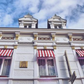 facade of a hotel with red and white awnings