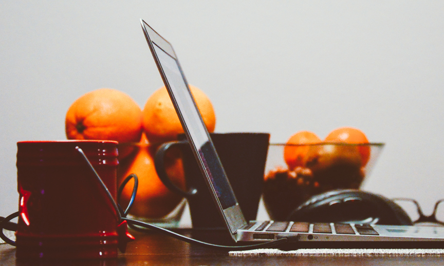a computer with a fruit bowl full of oranges next to it
