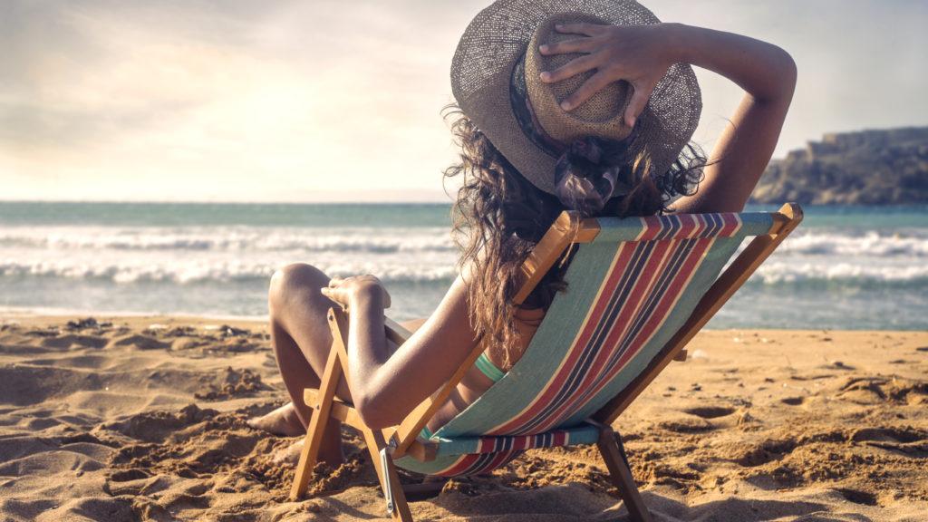 Ragazza con cappello che prende il sole in spiaggia