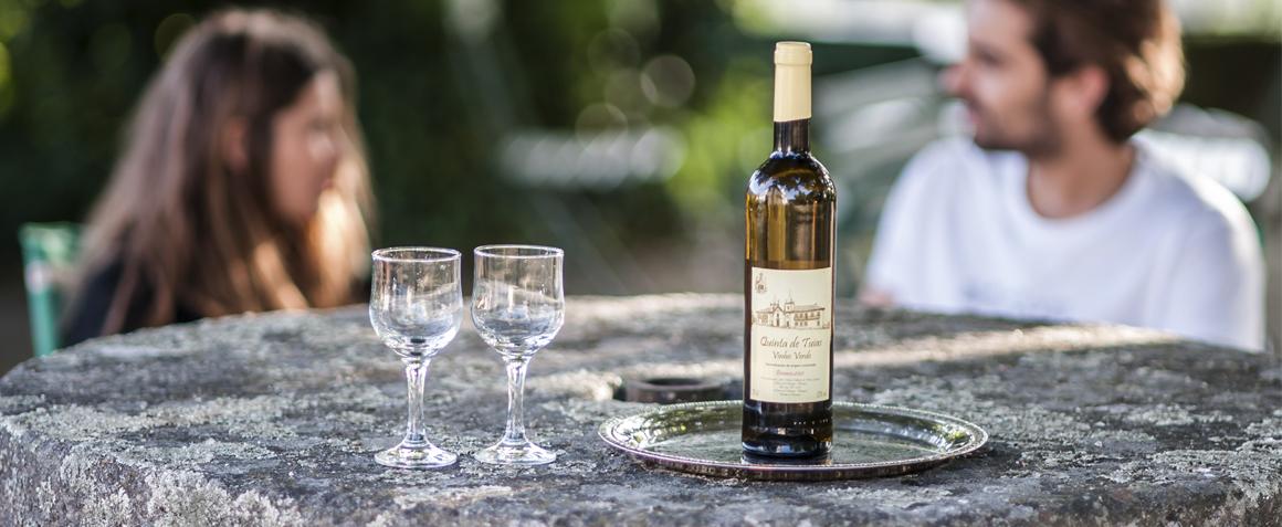 a couple enjoys wine on the terrace of casa do outeiro tuias