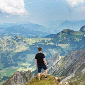 man on top of mountain looking at the view