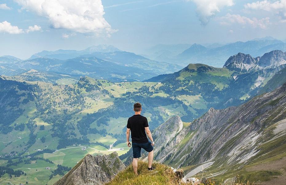 Uomo che guarda il panorama in cima a una montagna