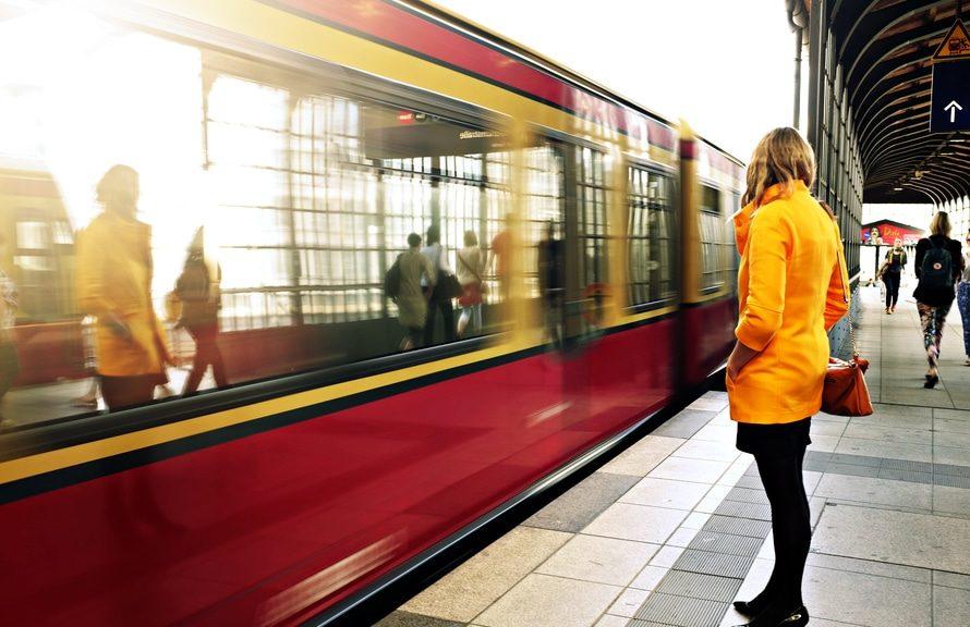 Donna con cappotto giallo che aspetta un treno