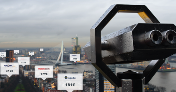 a set of sightseeing binoculars looks over a landscape of hotel rates