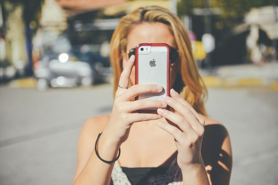 γυναίκα ταξιδιώτης χρησιμοποιεί το smart phone της για να βγάλει μια selfie