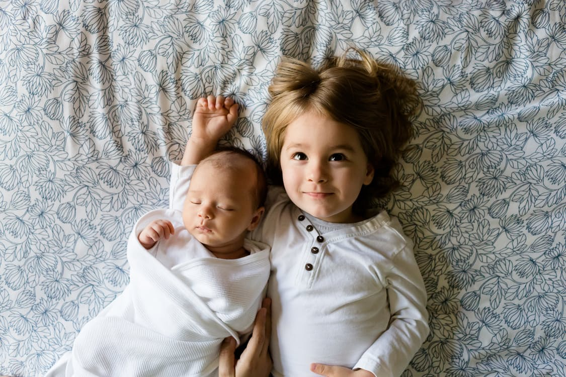a small child and her infant sister nestled in a hotel bed