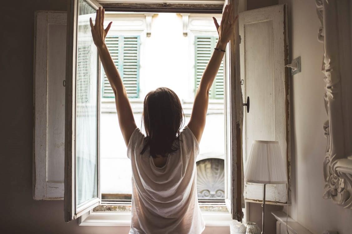 μια γυναίκα ξυπνάει και τεντώνεται κοντά σε ένα παράθυρο
