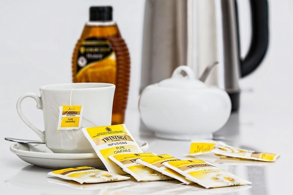 Juego de té y miel en una habitación de hotel