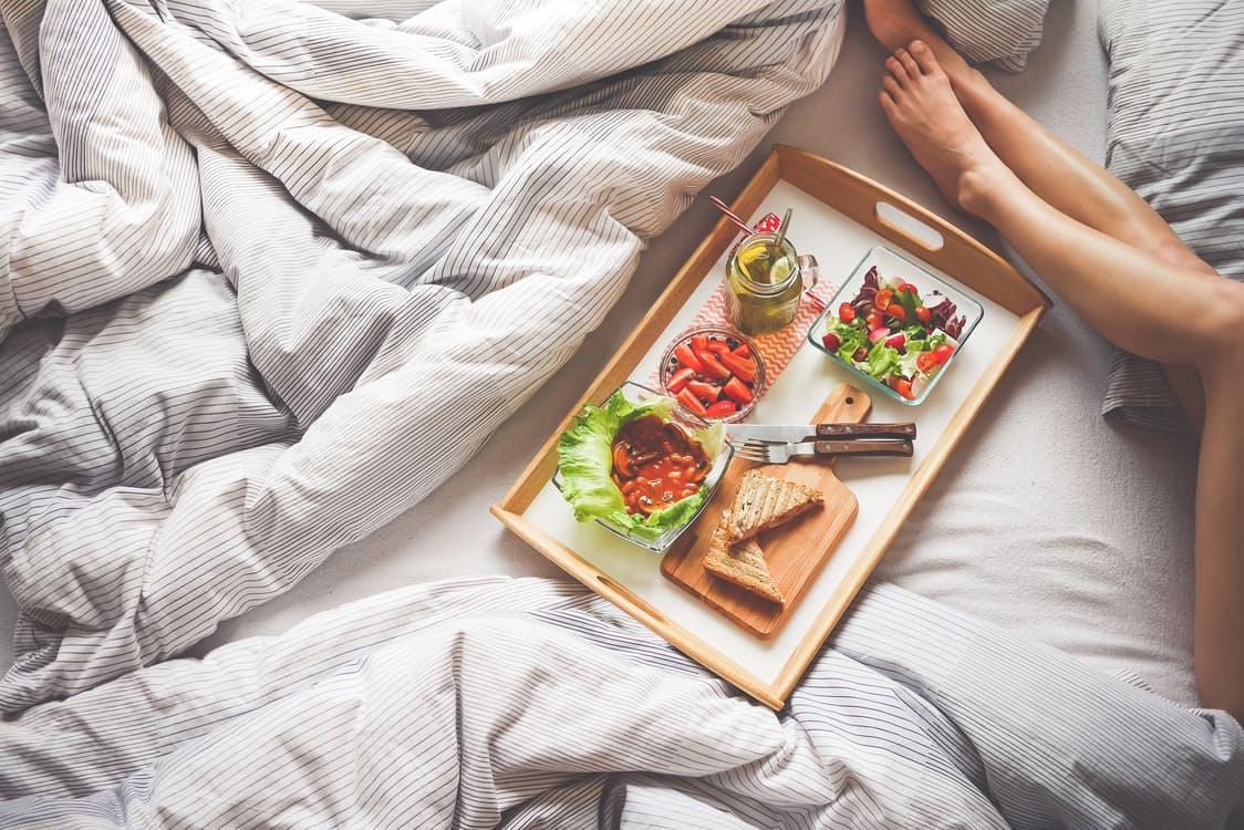 Un vassoio con la colazione sul letto di una stanza d'hotel