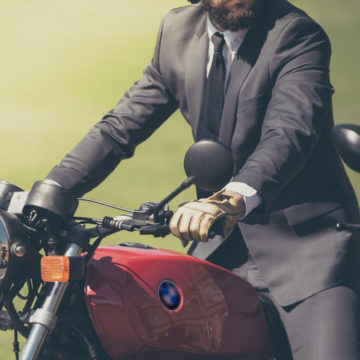 business traveller in a suit rides a motor bike
