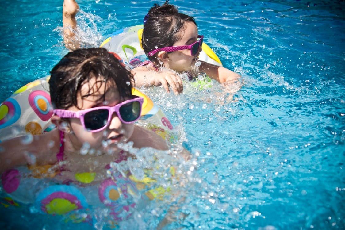 Zwei kleine Mädchen mit rosa Sonnenbrille schwimmen in einem Pool