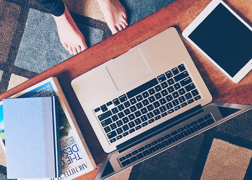 pés na frente de um computador