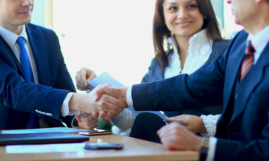 Business men and women shake hands