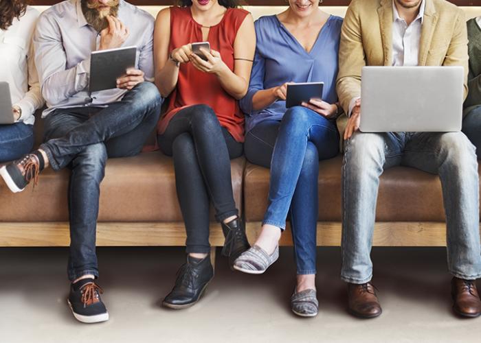 Verschiedene Reisende suchen auf Mobilgeräten nach dem idealen Hotel
