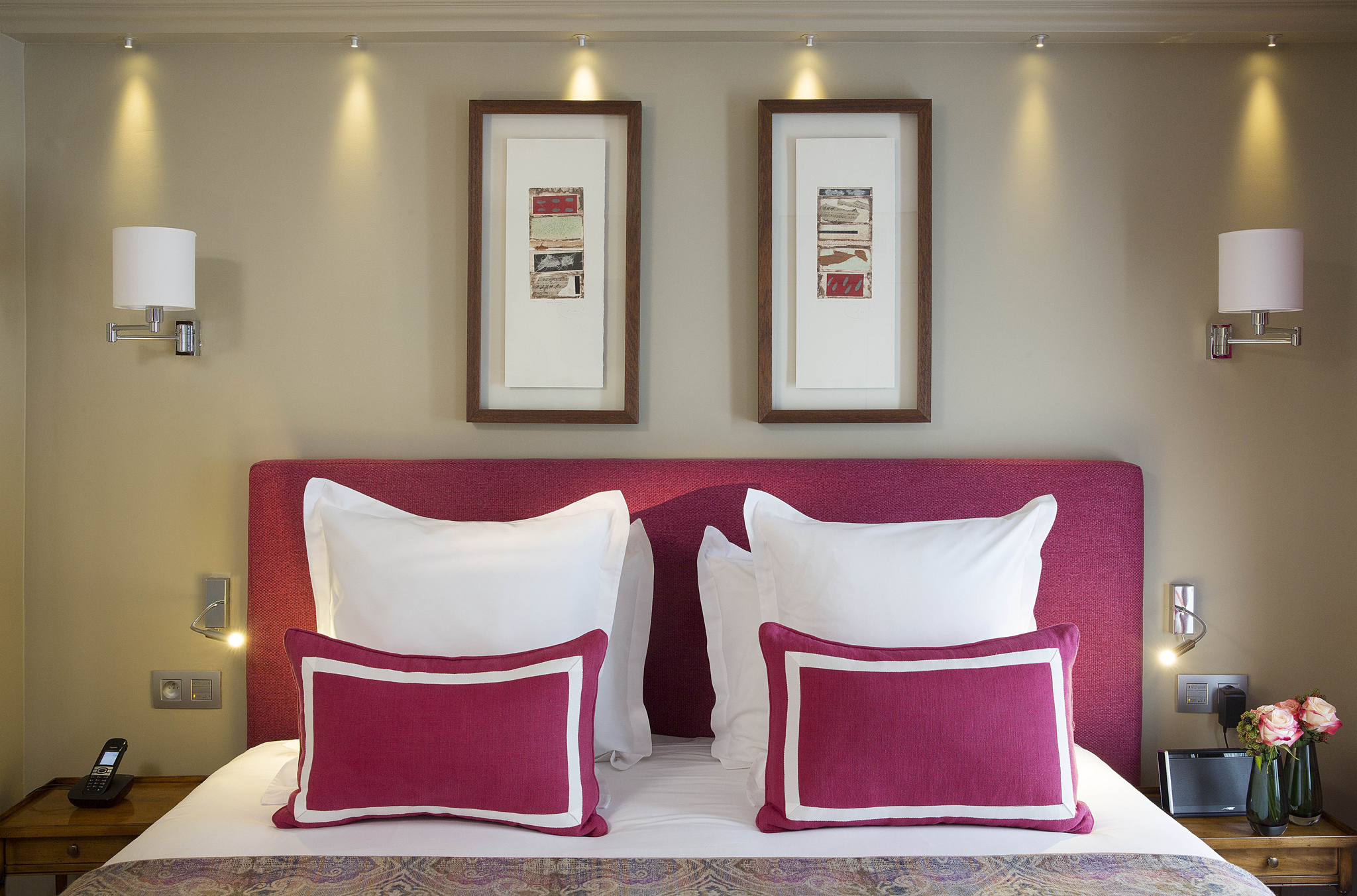 Tete de lit rose avec oreillers blancs et rouge.