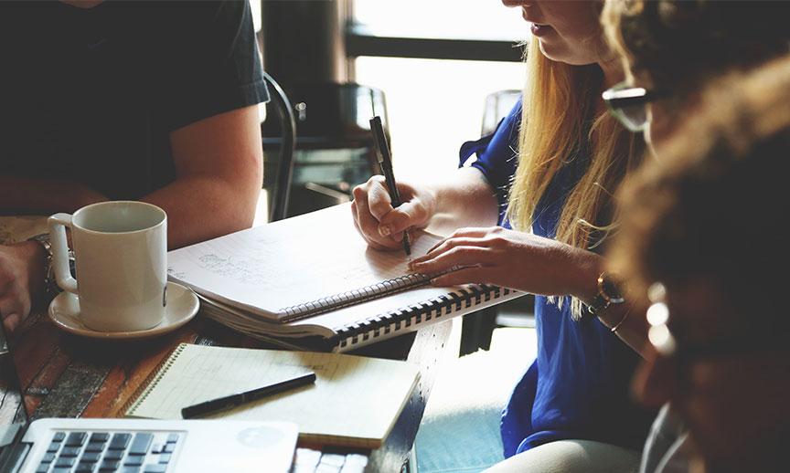 Uma hoteleira cria estratégias para a campanha por e-mail perfeita escrevendo ideias no caderno
