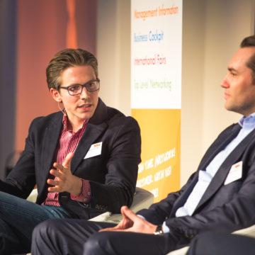 O Johannes Thomas κάθετε δίπλα στον Tobias Ragge ενώ μιλάει για τα πλεονεκτήματα του metasearch στην ITB στο Βερολίνο