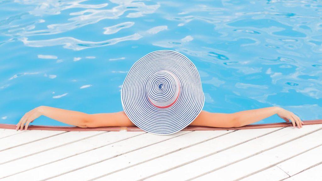 Θέα μιας γυναίκας που φοράει ένα μεγάλη καπέλο για τον ήλιο και χαλαρώνει στα ρηχά μιας πισίνας