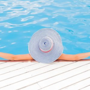 A bird's eye view of a women in a large sun hat lounging in the shallow end of a pool