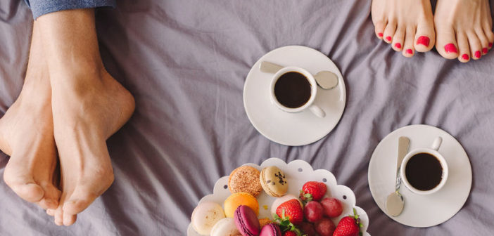 Millennials in a hotel having coffee and breakfast in bed