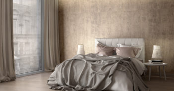 Hotel bed with grey, over-turned sheets.