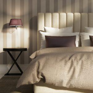 Letto di un'elegante camera d'hotel con carta da parati a righe