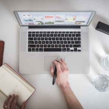 A birds-eye-view of a hotelier's desk set up for a webinar