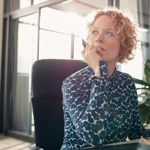 Mujer rubia con el pelo rizado pensando en un escritorio