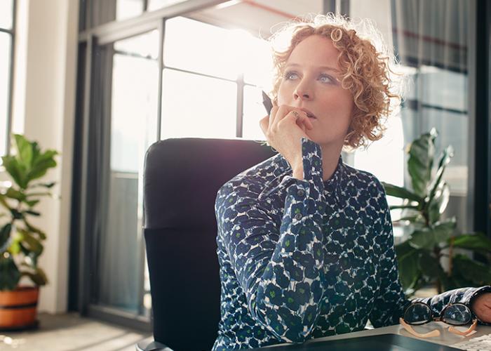 Ein Hotelier am Schreibtisch, die überlegt, welche Fragen sie zum trivago Hotel Manager und ihrem Account stellen kann