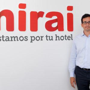 Mirai CEO Pablo Delgado poses in front of his company's logo