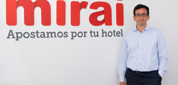 Mirai CEO Pablo Delgado poses in front of his company's logo