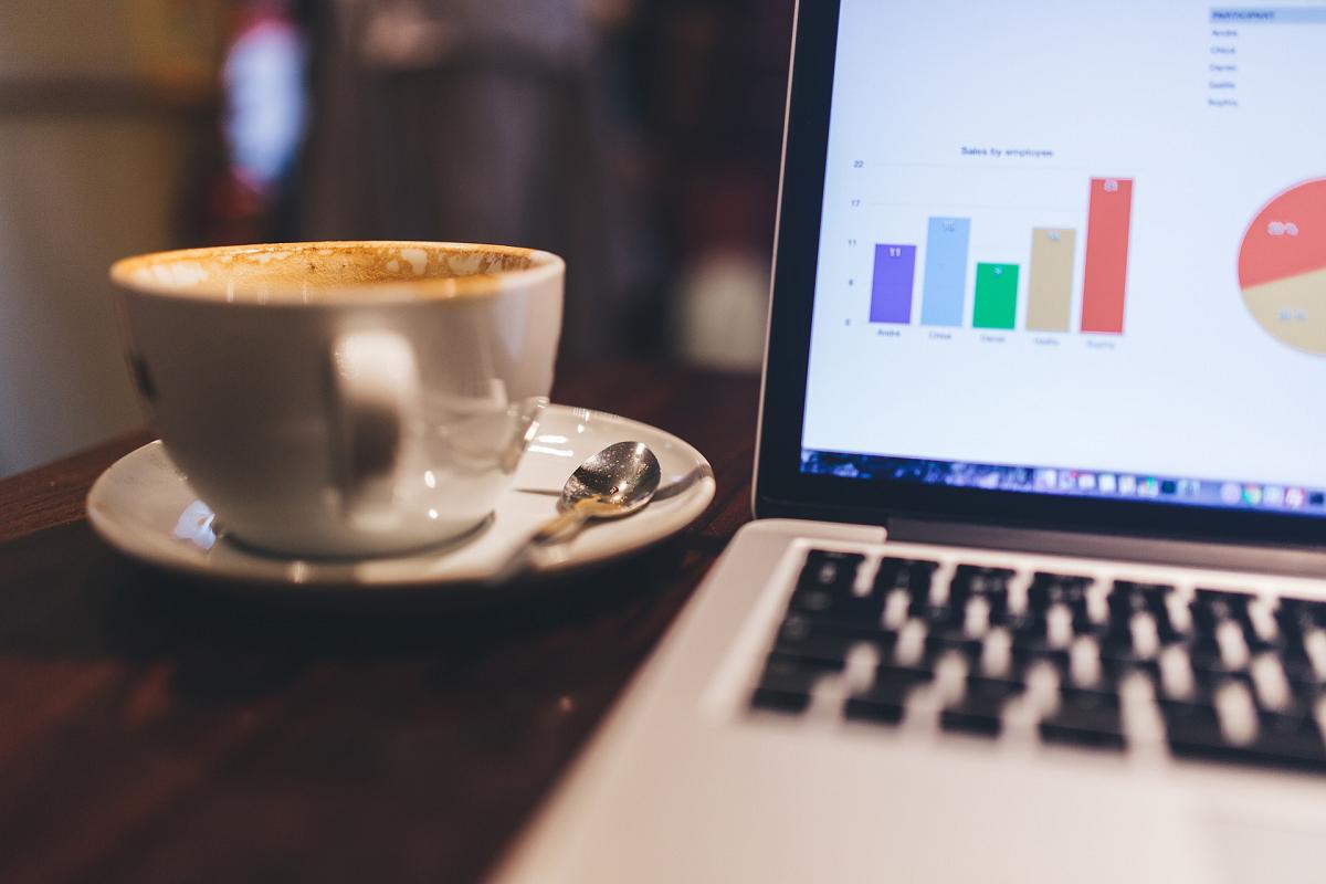 un ordinateur ouvert montrant les résultats des campagnes marketing, à côté d'une tasse de café