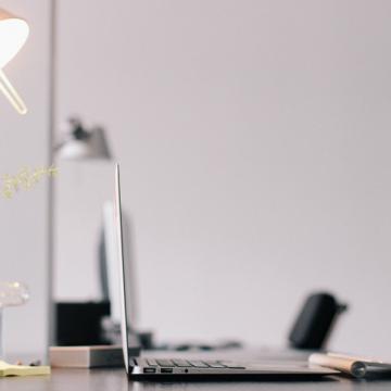 Un ordinateur ouvert sur un bureau, avec une lampe moderne et une plante verte