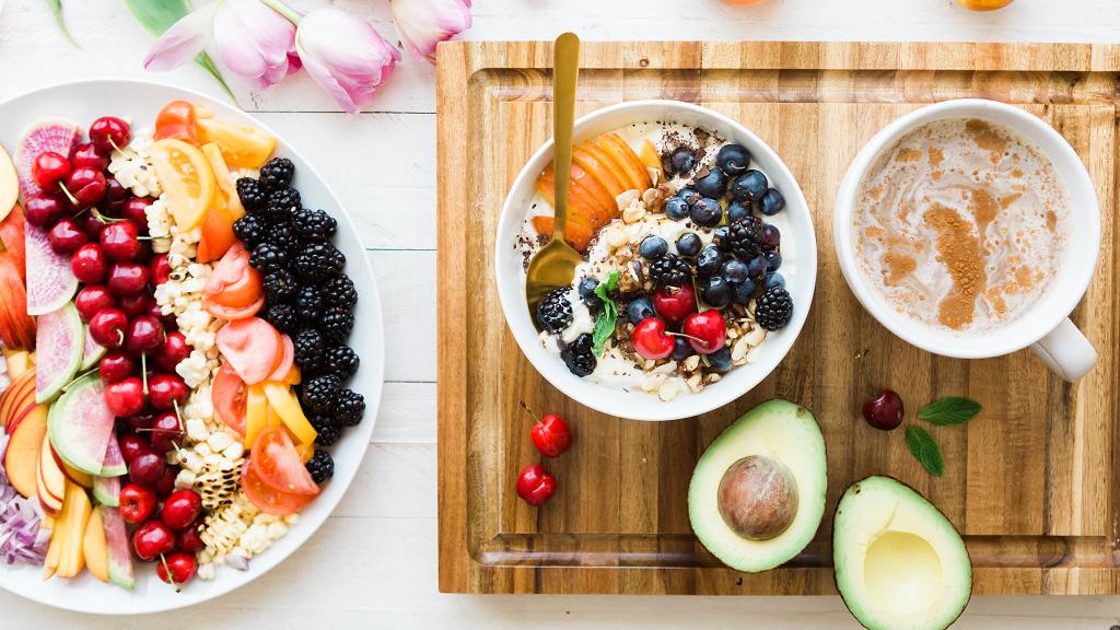 Eine Servierplatte bis zum Rand gefüllt mit exotischen Früchten neben einer aufgeschnittenen Avocado und einer Schüssel Haferflocken