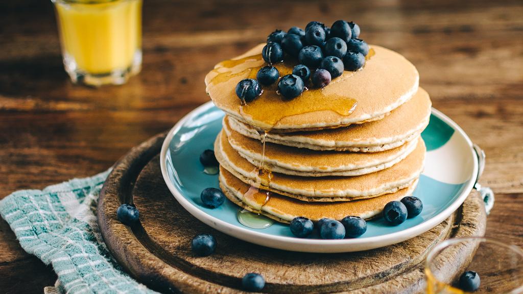 Une assiette de pancakes avec des myrtilles et un verre de jus d'orange