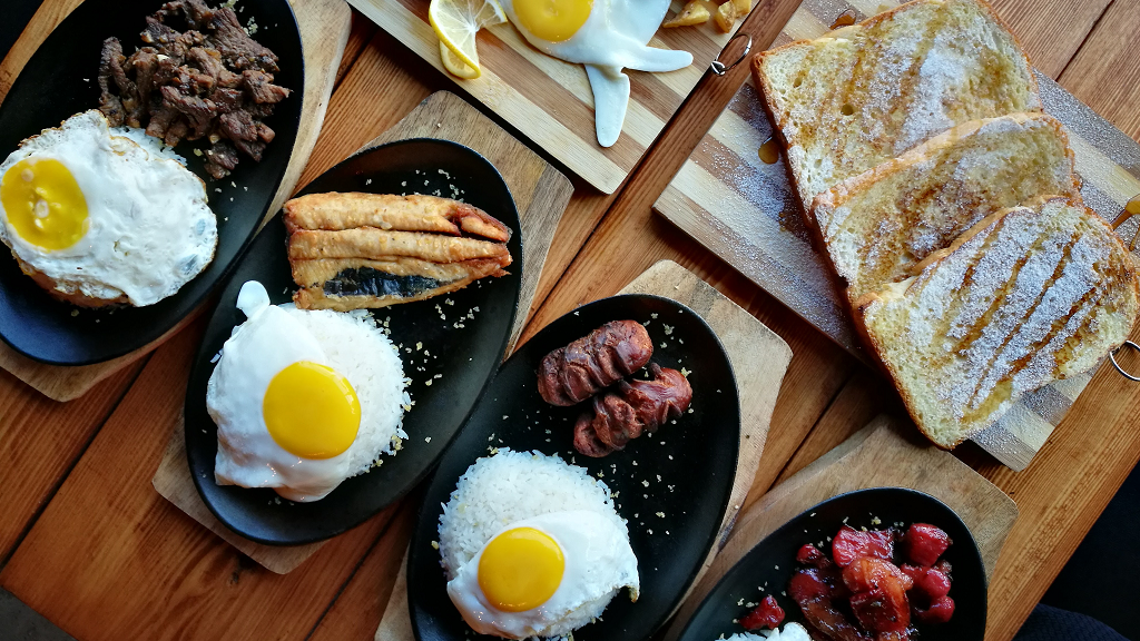 Skillets with fried eggs and different breakfast meats lined up on a table