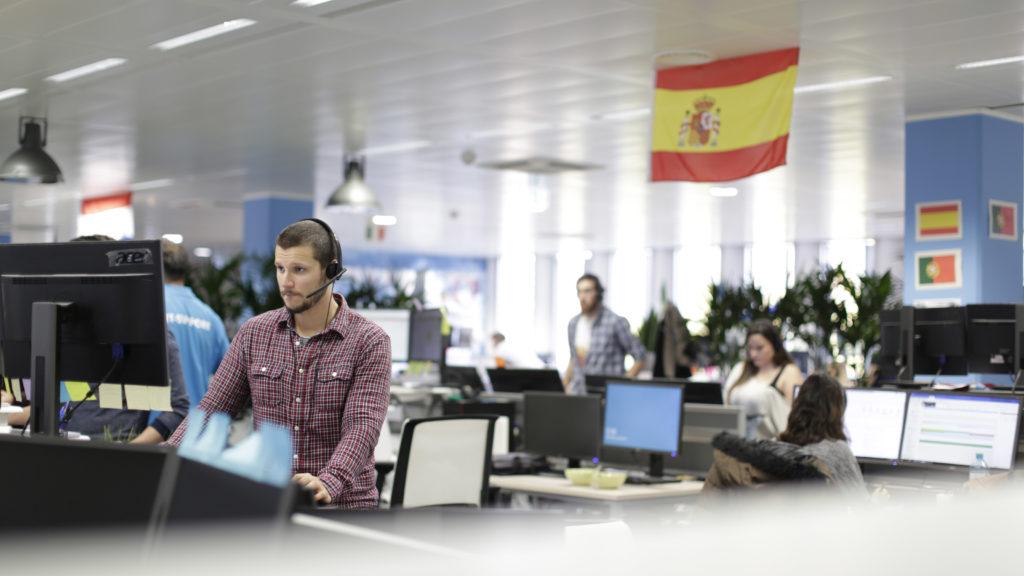 Hombre trabajando en el ordenador con la bandera de Portugal y España