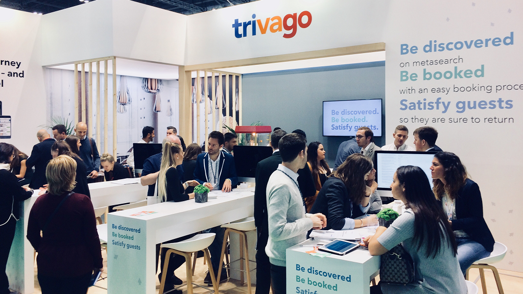 trivago's stand full of people talking in small groups