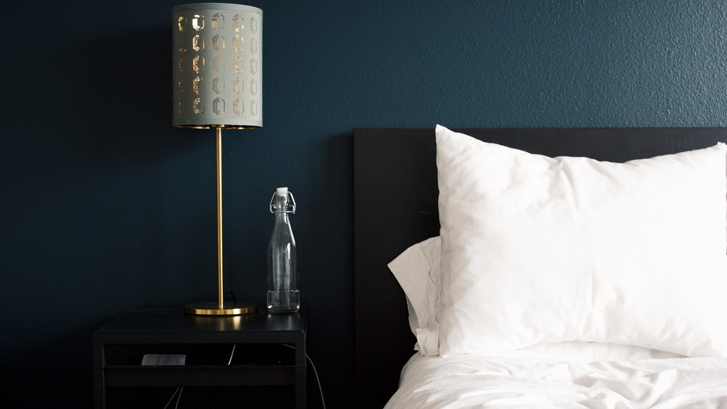 A modern hotel bed with white linens