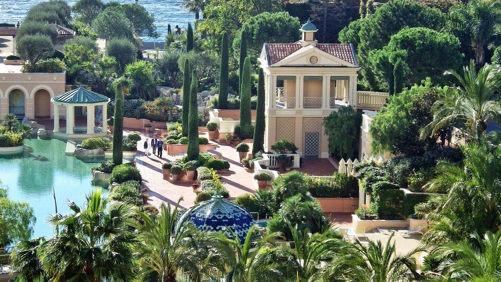 Balcones de un hotel con vistas a un jardín con flores y palmeras