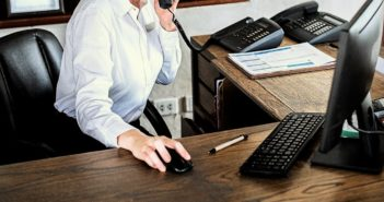 Responsable de un hotel independiente utiliza el teléfono y el ordenador