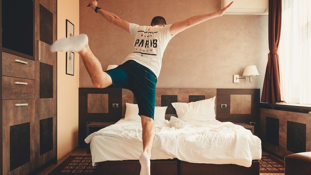 Φωτογραφία ενός πελάτη που ετοιμάζεται να απολαύσει το κρεβάτι ενός ξενοδοχείου