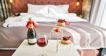 A hotel room with cupcakes and wine