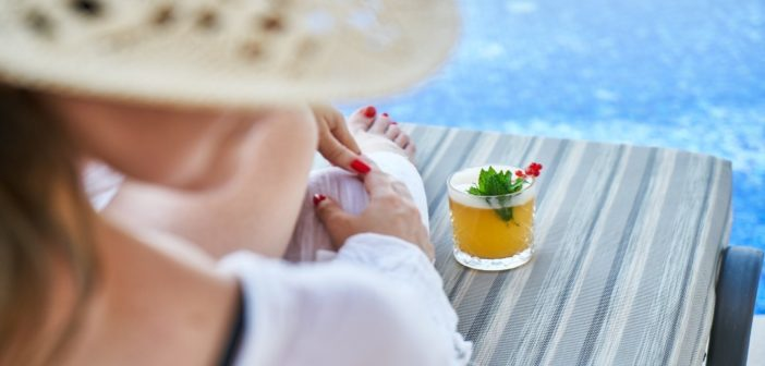 A woman by the pool with a drink
