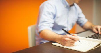 Homem trabalhando em um notebook e fazendo anotações