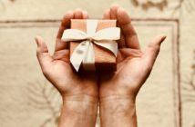 Hände, die ein Geschenk halten